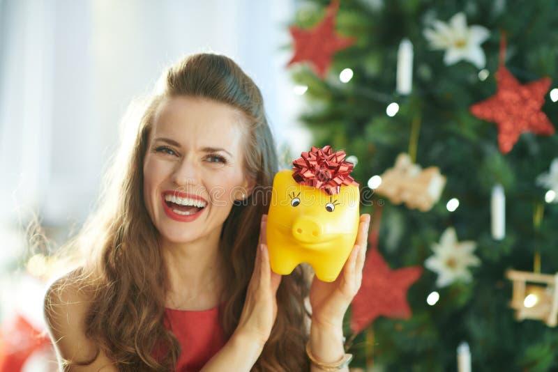 Jeune femme de sourire montrant la tirelire jaune avec l'arc rouge images stock