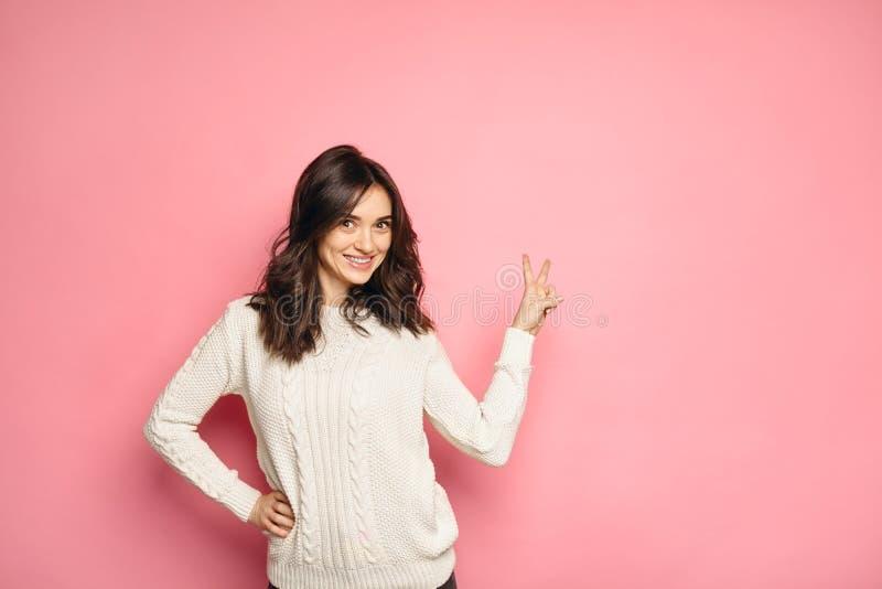 Jeune femme de sourire montrant le signe de main de paix photo stock