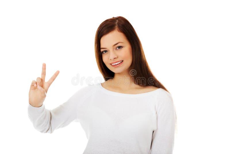 Jeune femme de sourire montrant le signe de victoire image stock