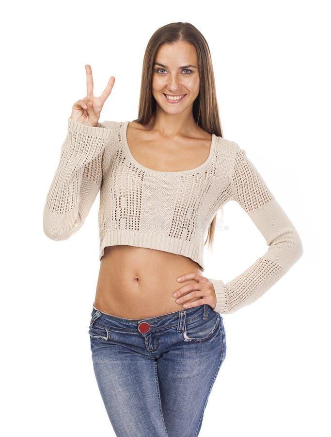 Jeune femme de sourire montrant le signe de victoire ou de paix photographie stock