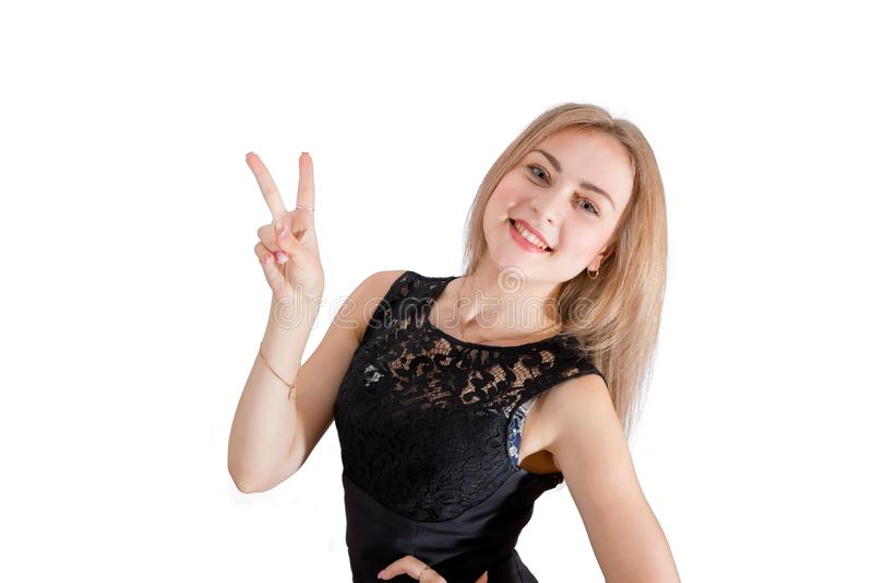 Jeune femme de sourire montrant le signe de main de paix image stock