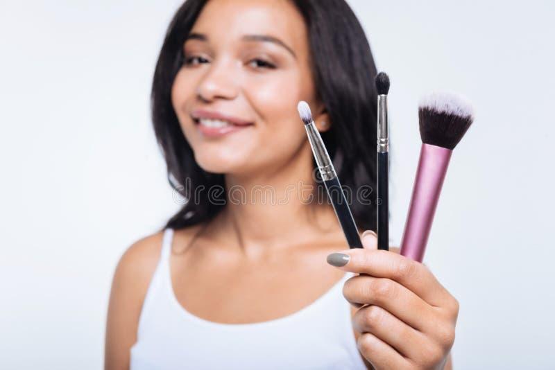 Jeune femme de sourire montrant trois brosses de maquillage photos stock