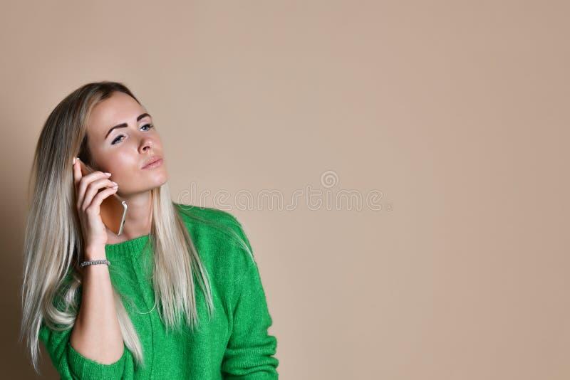 Jeune femme de sourire parlant au téléphone portable regardant l'espace vide de copie photos libres de droits