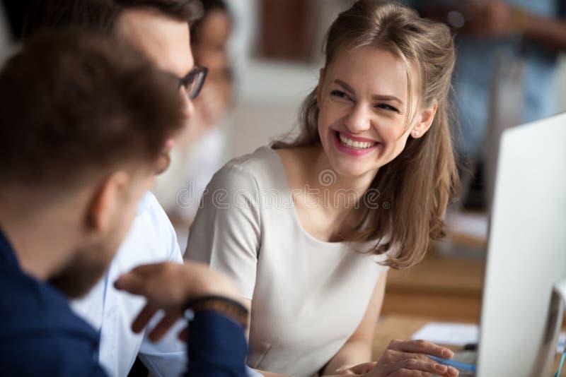 Jeune femme de sourire parlant avec des collègues sur le lieu de travail partagé photo libre de droits