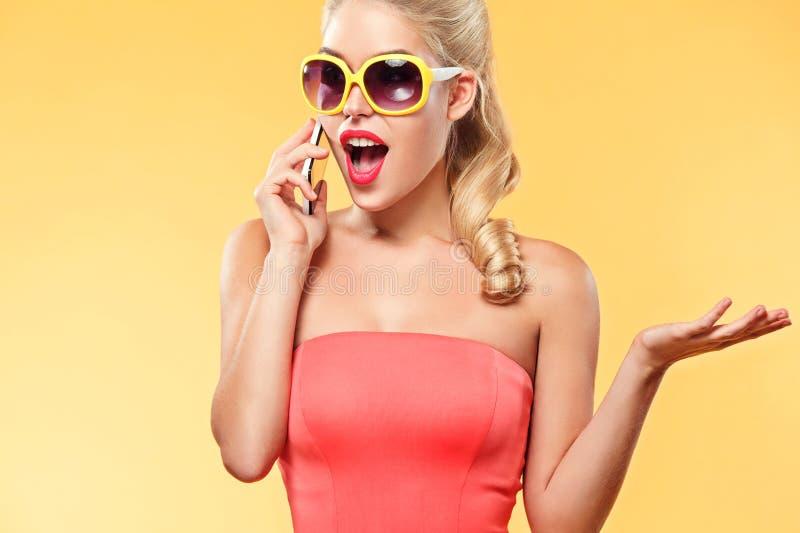 Jeune femme de sourire parlant par le téléphone portable au sujet de la vente vendredi noir Fille avec l'espace jaune de fond et  photo libre de droits