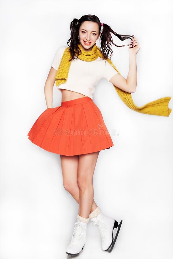 Jeune femme de sourire patinant dans une jupe et une écharpe sur le fond d'isolement photos stock