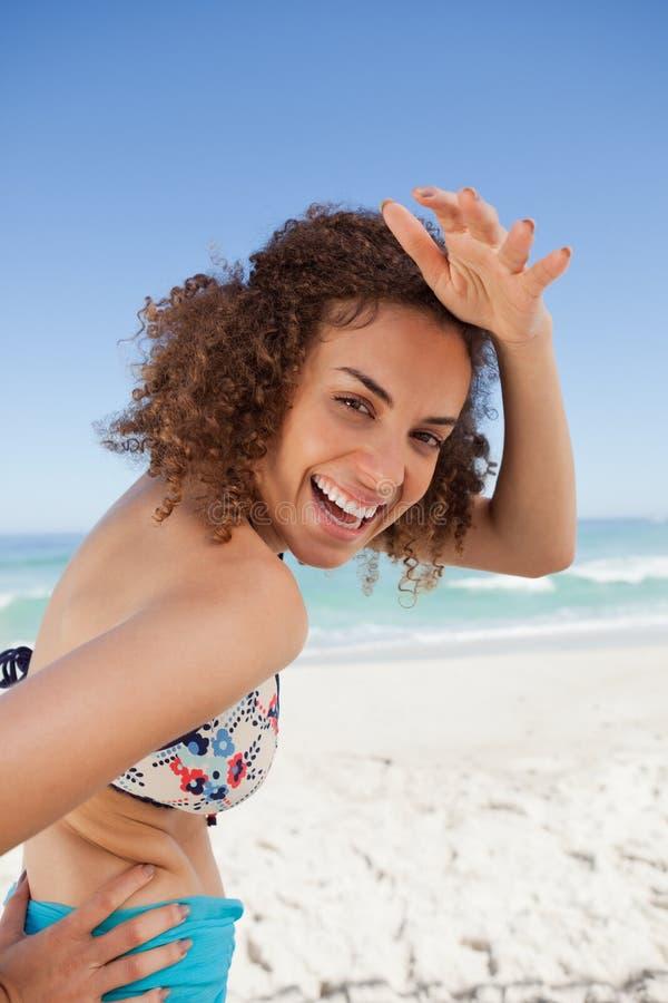 Jeune femme de sourire plaçant sa main sur son front pour regarder image stock