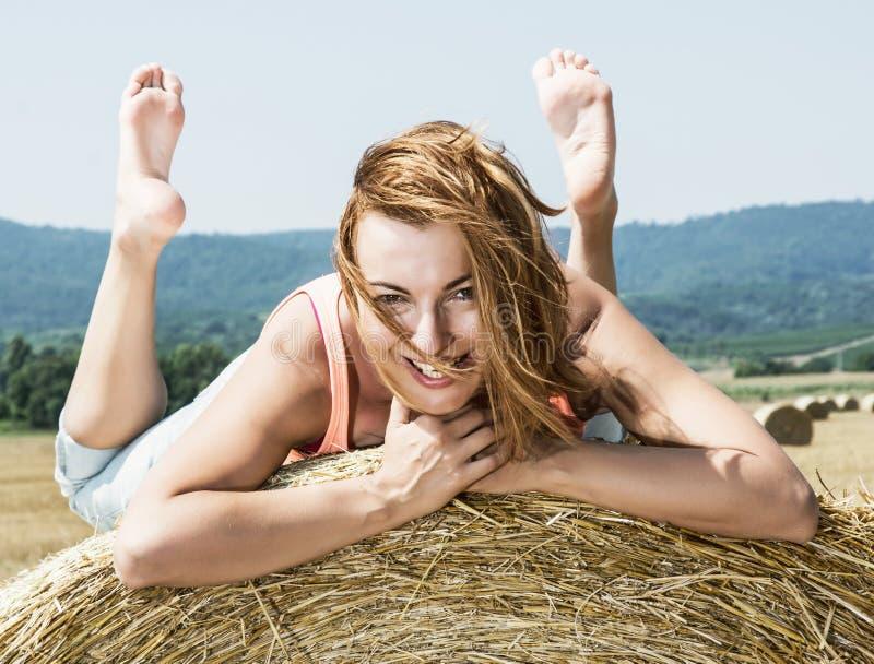 Jeune femme de sourire posant avec la pile de paille et d'apprécier photos libres de droits