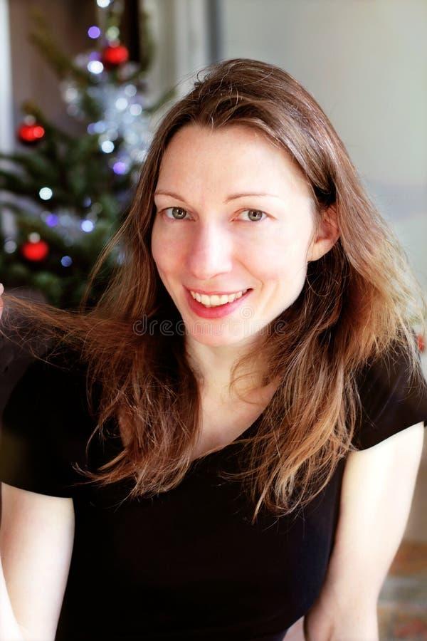 Jeune femme de sourire près d'arbre de Noël portrait gai photographie stock libre de droits