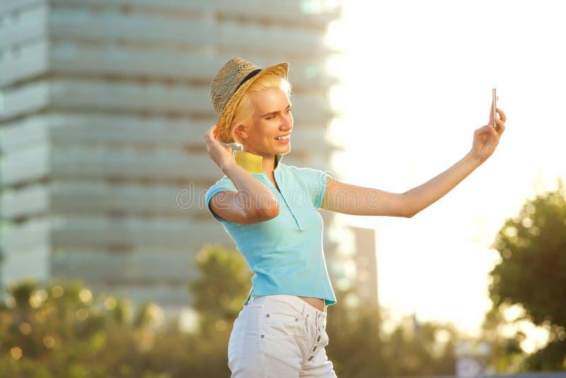 Jeune femme de sourire prenant le portrait de selfie dehors image stock
