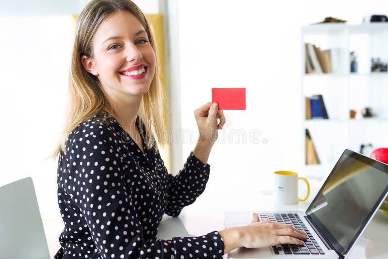 Jeune femme de sourire regardant la caméra tout en tenant la carte de crédit rouge pour faire des emplettes en ligne avec l'ordin photos stock