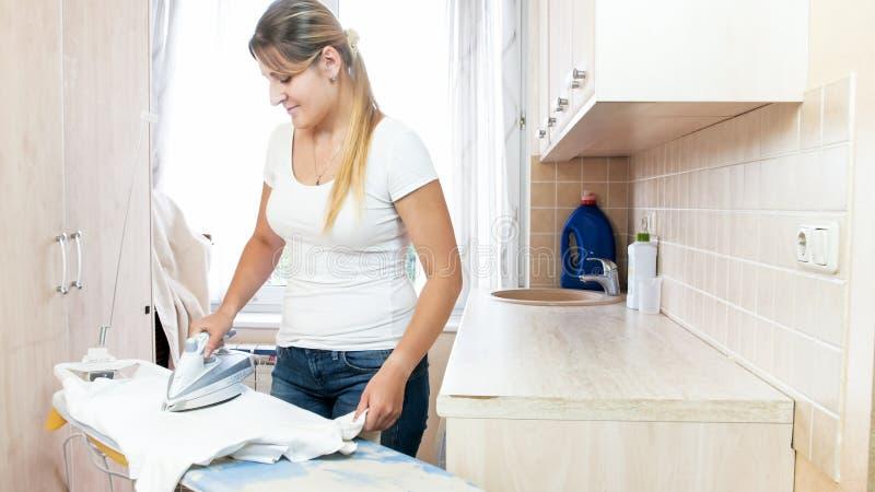 Jeune femme de sourire repassant les vêtements propres après blanchisserie photographie stock libre de droits