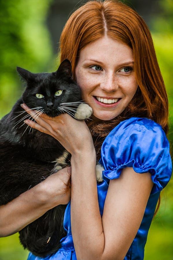 Jeune femme de sourire rousse avec le chat noir photos libres de droits