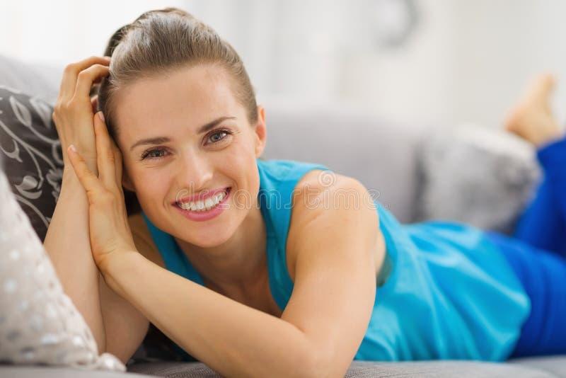 Jeune femme de sourire s'étendant sur le sofa dans le salon photos stock