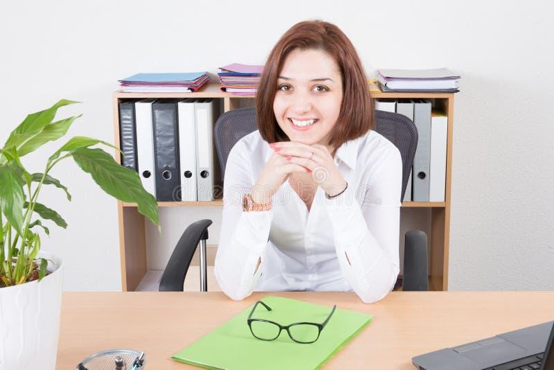 Jeune femme de sourire s'asseyant à son bureau dans le bureau photo stock