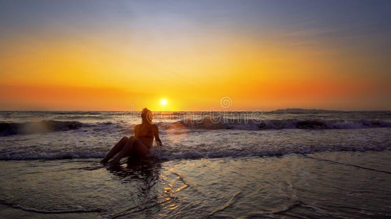 Jeune femme de sourire s'asseyant dans des vagues de mer et détendant aux vacances d'été au coucher du soleil photos stock