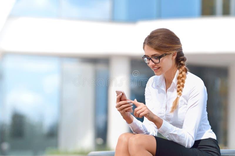 Jeune femme de sourire s'asseyant en dehors du message textuel de lecture au téléphone portable image stock