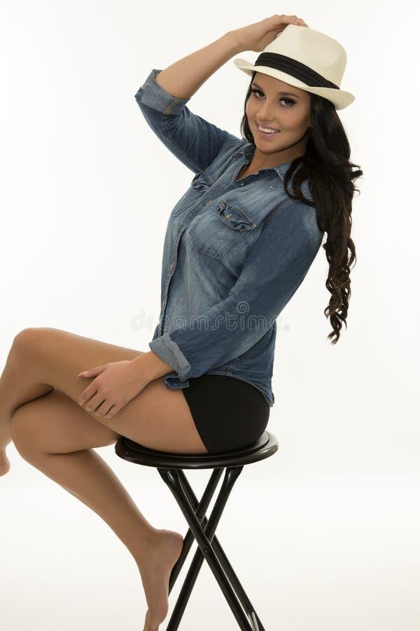 Jeune femme de sourire s'asseyant sur le tabouret image stock