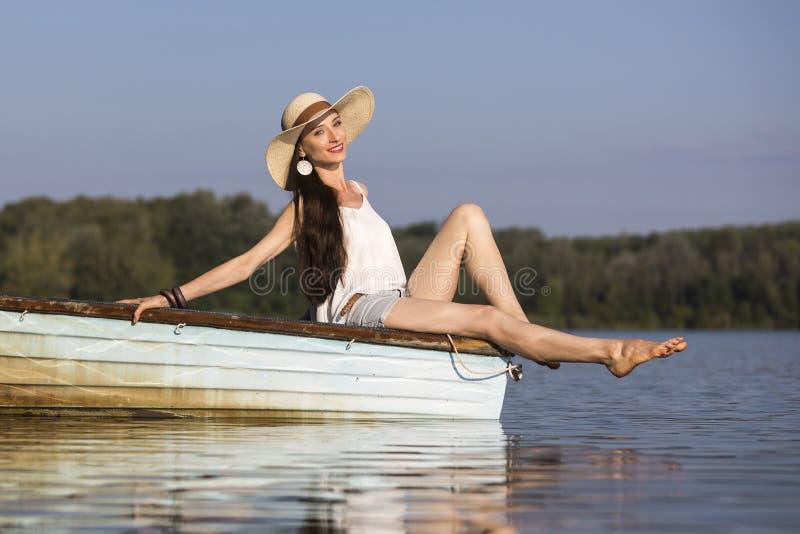 Jeune femme de sourire s'asseyant sur un bateau en été photos libres de droits