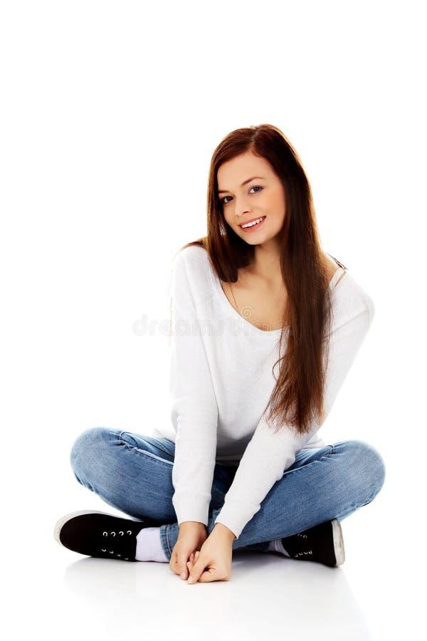 Jeune femme de sourire s'asseyant sur un plancher avec des jambes croisées photographie stock