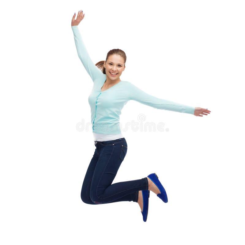 Jeune femme de sourire sautant en air images libres de droits
