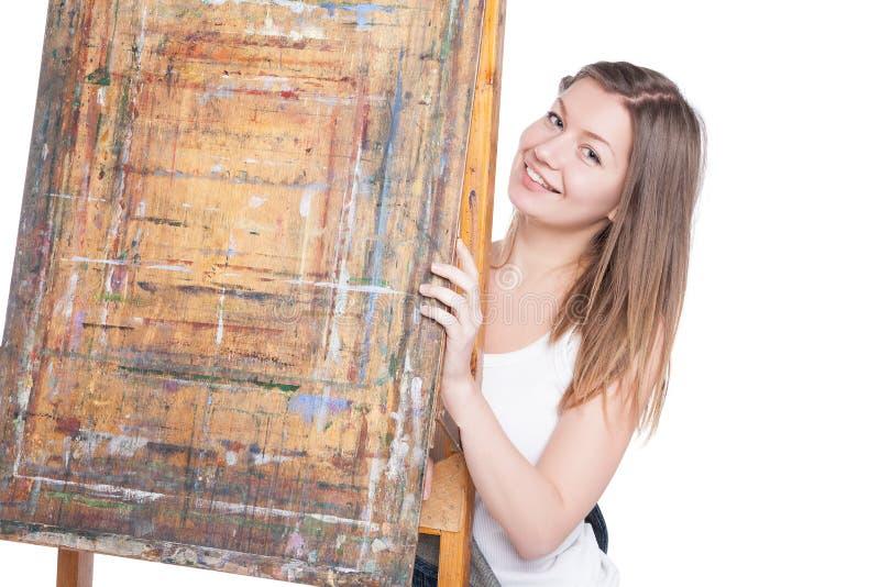 Jeune femme de sourire se cachant derrière le chevalet images stock