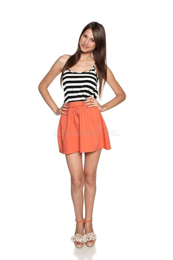 Jeune femme de sourire se tenant dans l'habillement d'été image stock