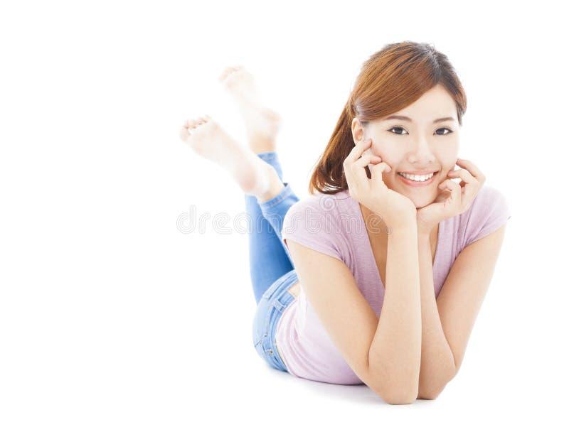 Jeune femme de sourire se trouvant sur l'étage photographie stock