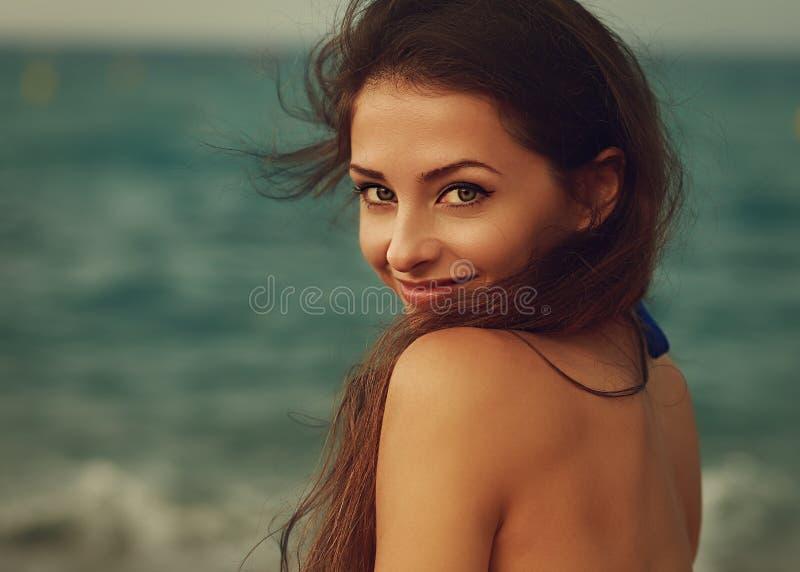 Jeune femme de sourire semblant heureuse sur la mer images libres de droits