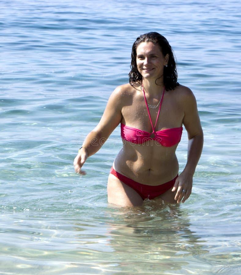 Jeune femme de sourire sortant de l'eau de mer photos libres de droits