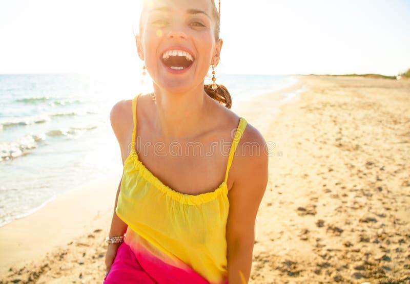 Jeune femme de sourire sur la plage dans la soirée ayant le temps d'amusement photos stock