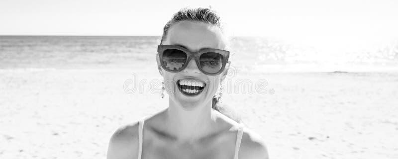 Jeune femme de sourire sur le bord de la mer photographie stock libre de droits