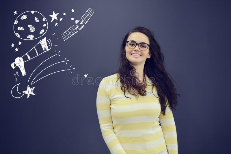 Jeune femme de sourire sur le fond de gris bleu avec des icônes d'universum photo stock