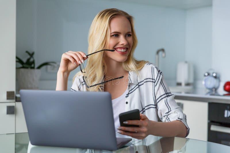 jeune femme de sourire tenant des lunettes et regardant loin tout en travaillant avec les dispositifs numériques photographie stock libre de droits