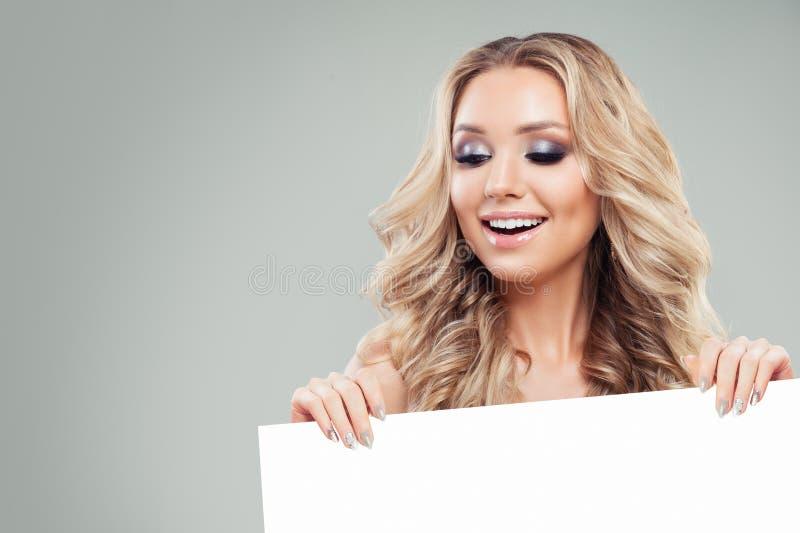 Jeune femme de sourire tenant la bannière vide blanche de papier de conseil photos libres de droits