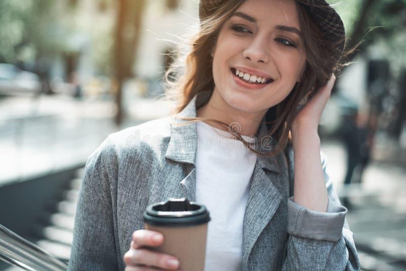 Jeune femme de sourire tenant la boisson chaude dehors image libre de droits