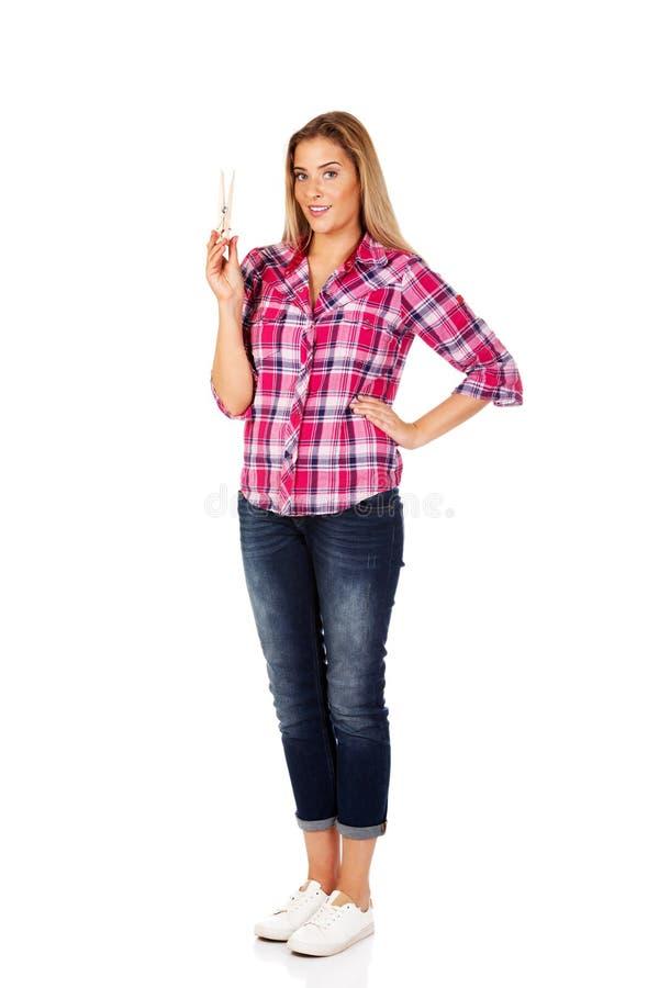 Jeune femme de sourire tenant la goupille énorme de tissu photos stock