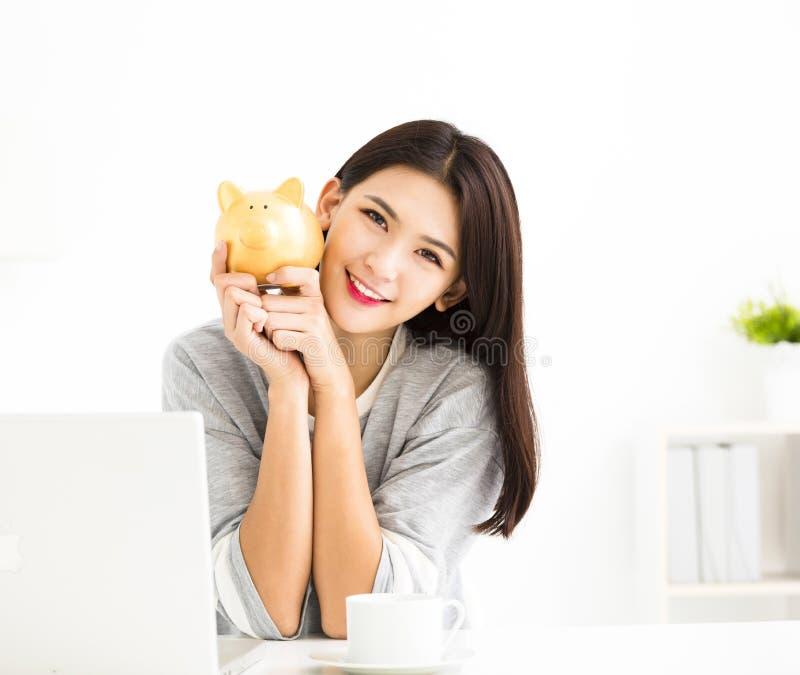 Jeune femme de sourire tenant la tirelire photos stock