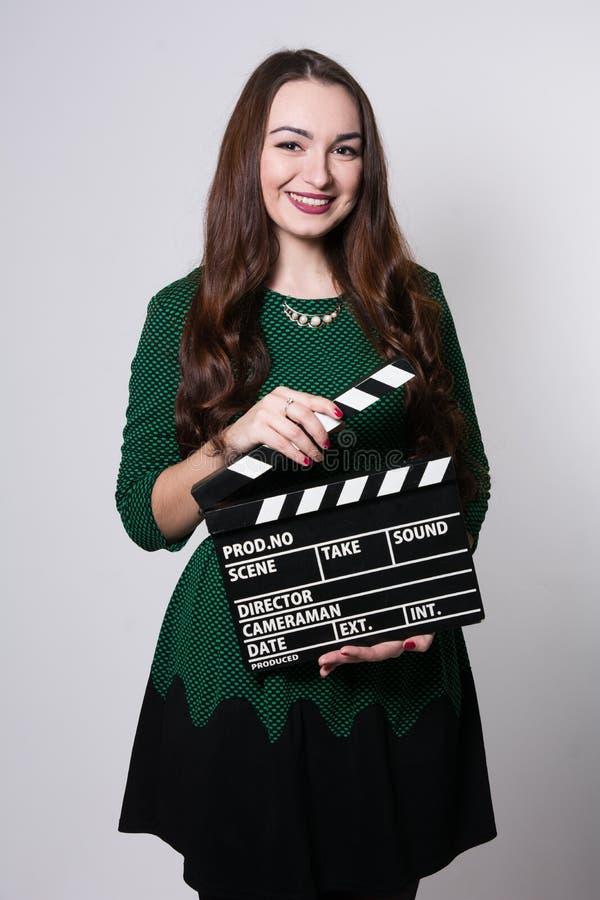 Jeune femme de sourire tenant un clapet de film photos stock
