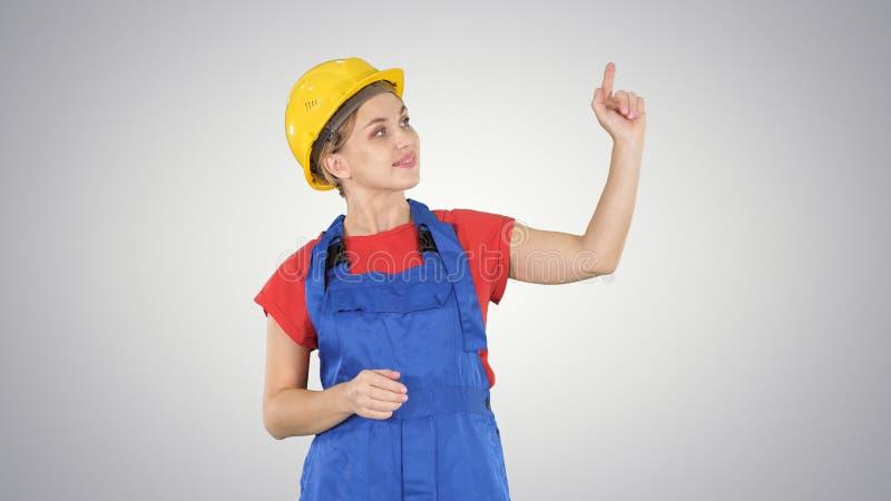 Jeune femme de sourire de travailleur se dirigeant sur les boutons imaginaires sur l'écran imaginaire sur le fond de gradient photo stock