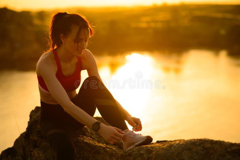 Jeune femme de sports attachant les chaussures de course et se préparant à la course de traînée au coucher du soleil Mode de vie  photographie stock libre de droits