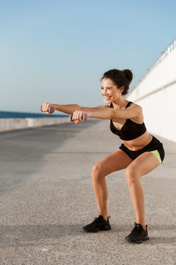 Jeune femme de sports faire des exercices avec des haltères dehors sur la plage photo libre de droits