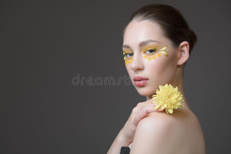 Jeune femme de station thermale Fleurs sur son visage Le concept du soin de peau et de corps Santé parfaite de peau photo stock