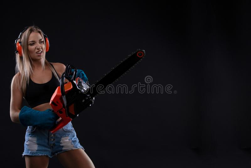 Jeune femme de tentation posant avec la tronçonneuse photographie stock libre de droits