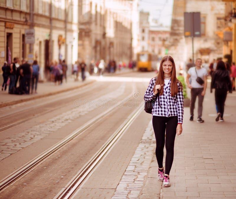 Jeune femme de touristes avec la promenade de sac à dos par la rue dans la vieille ville de l'Europe, style de mode d'été photographie stock
