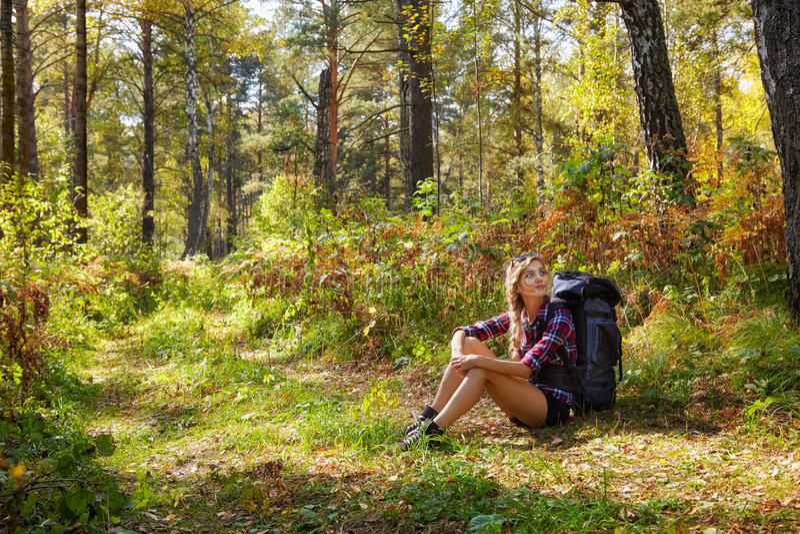 Jeune femme de touristes blonde avec un sac à dos se reposant sur le sidel image libre de droits