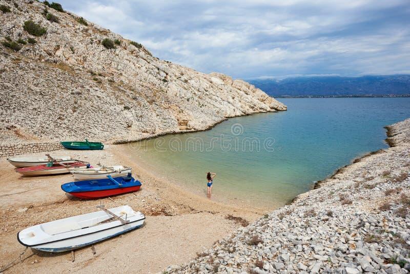Jeune femme de touristes dans la position de costume de natation au bord de l'eau photo libre de droits