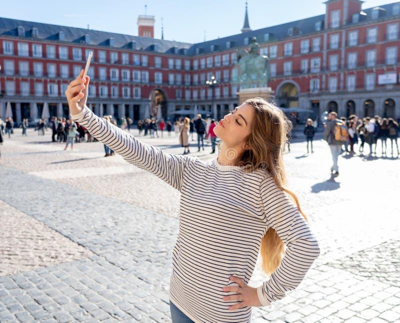 Jeune femme de touristes heureuse attirante prenant le selfie ou la vidéo à Madrid Espagne ayant l'amusement photographie stock libre de droits