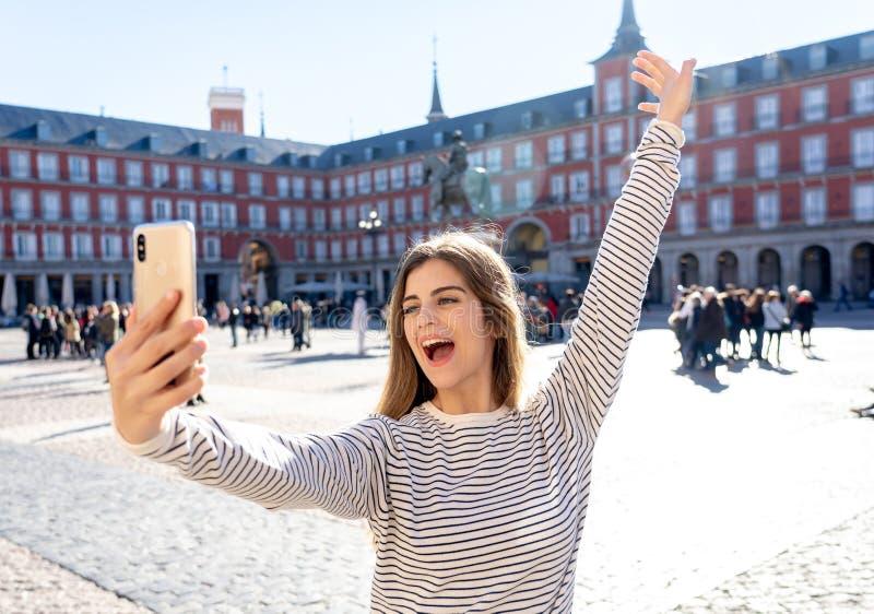 Jeune femme de touristes heureuse attirante prenant le selfie ou la vidéo à Madrid Espagne ayant l'amusement images libres de droits