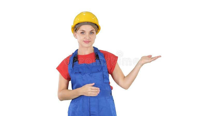 Jeune femme de travailleur de constructeur présent montrant le produit avec ses mains de ses côtés sur le fond blanc photos libres de droits